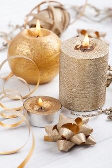 Velas aromáticas encendidas doradas y juguetes de navidad sobre fondo rústico de madera