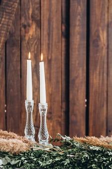 Velas blancas altas en candelabros de cristal sobre fondo con textura de madera rústica envejecida.