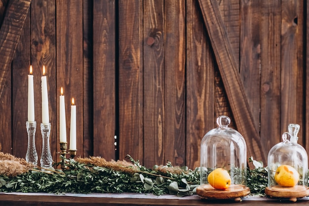Velas blancas altas en candelabros de cristal sobre fondo con textura de madera rústica.