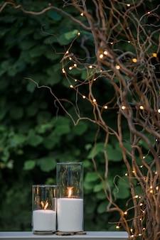 Velas blancas en floreros altos de pie bajo ramas secas con fuegos