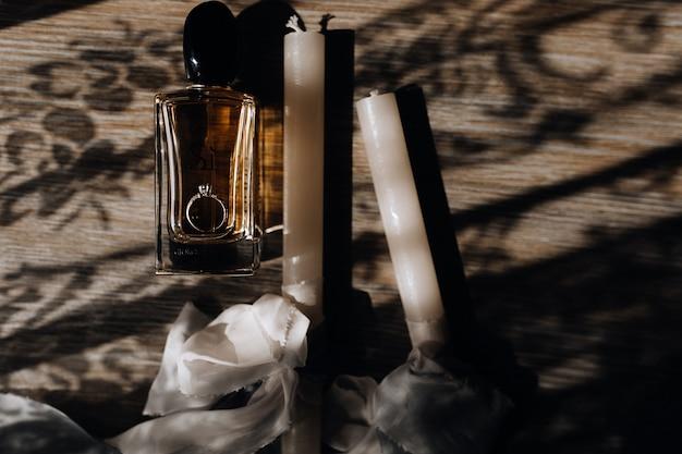 Velas de boda ceremoniales con cintas blancas, anillo de compromiso y perfume en el piso de madera.