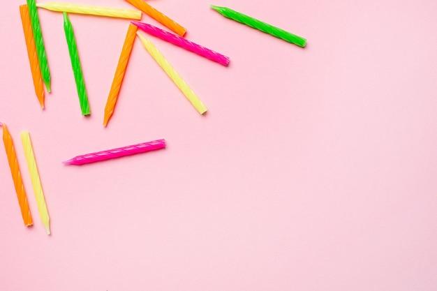 Velas de colores para tarta de cumpleaños sobre un fondo rosa
