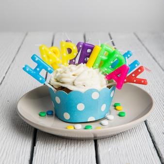 Velas coloridas de feliz cumpleaños insertadas en una magdalena en un plato sobre la mesa de madera