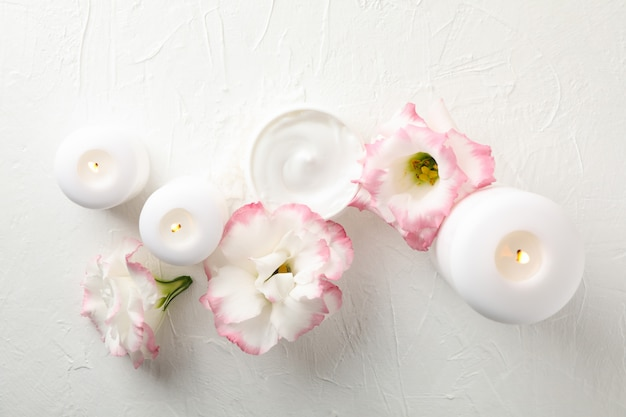 Velas, crema y flores sobre fondo blanco, espacio para texto