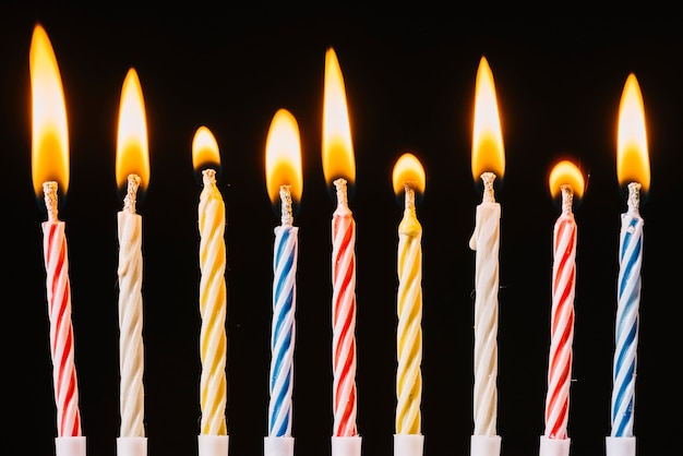 Velas de cumpleaños ardientes sobre fondo negro