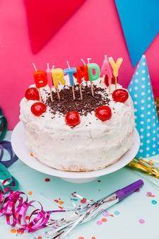 Velas de cumpleaños en pastel blanco con decoración de fiesta