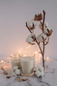 Velas decoradas con ramitas de algodón y equipos de iluminación en superficie de mármol.