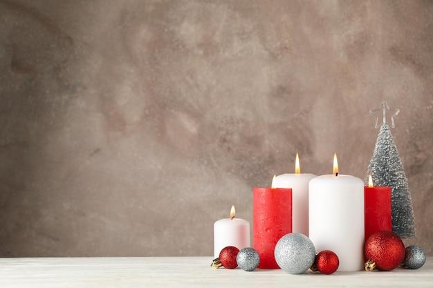 Velas encendidas, árbol de navidad y bolas contra marrón, espacio para texto