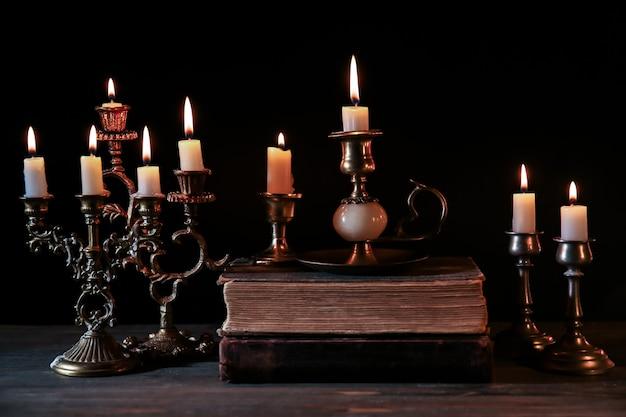 Velas encendidas y biblias en la mesa de madera