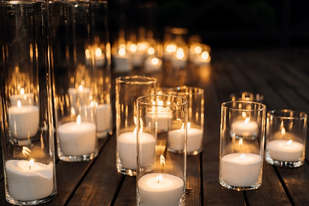Velas encendidas en el candelabro de vidrio transparente en el piso