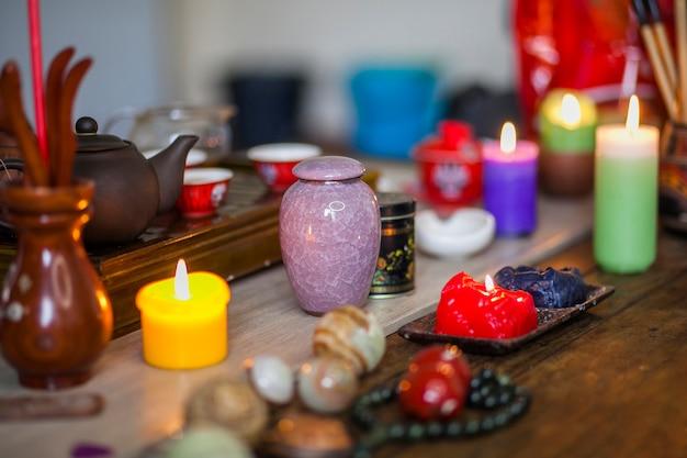 Velas encendidas de colores; jarrón de cerámica y terapias chinas sobre mesa de madera.