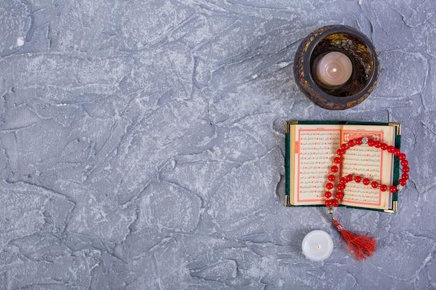 Velas encendidas con cuentas rojas de kuran y rosario sobre fondo gris texturizado