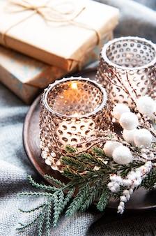 Velas encendidas decorativas de navidad, ramas de abeto y cajas de regalo sobre superficie de lana gris