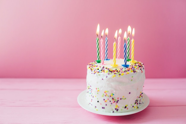 Velas encendidas en la torta blanca