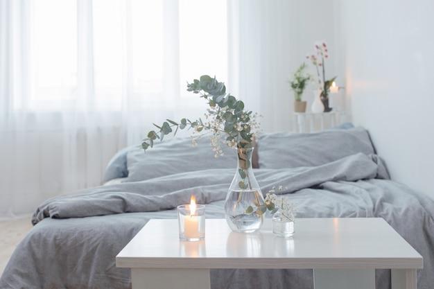 Velas encendidas y eucalipto en florero de vidrio en dormitorio blanco