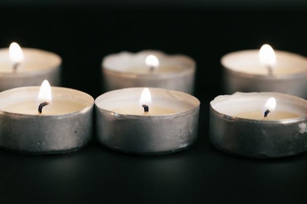 Velas encendidas en la noche. velas blancas ardiendo en la oscuridad