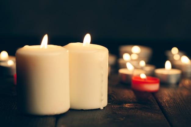 Velas encendidas en la oscuridad sobre negro. conmemoración