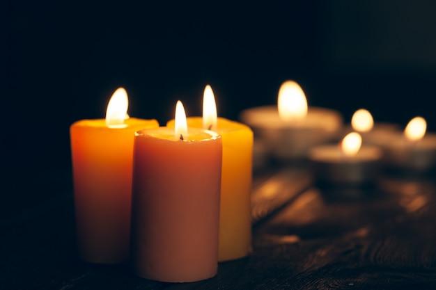 Velas encendidas en la oscuridad sobre negro