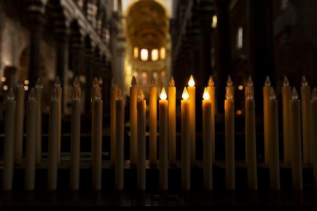 Velas encendidas en el oscuro interior del templo. de cerca.