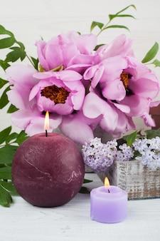 Velas encendidas, peonías y flores lilas.