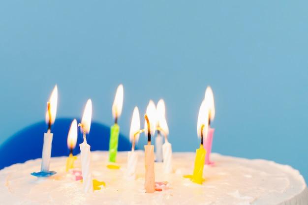 Velas encendidas en primer plano de pastel de cumpleaños