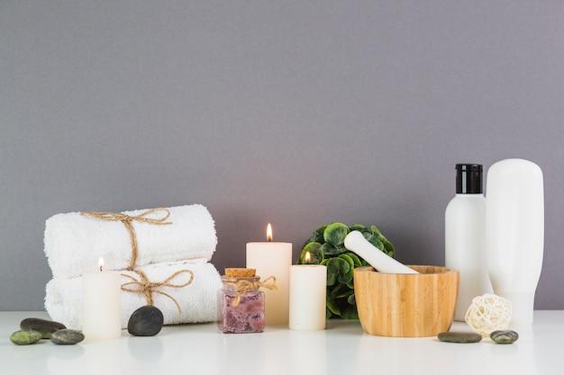 Velas encendidas y productos de belleza frente a la pared gris.