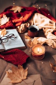 Velas encendidas, taza de té caliente, libro abierto y vasos a cuadros en la cama