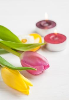 Velas encendidas y tulipanes rosados amarillos