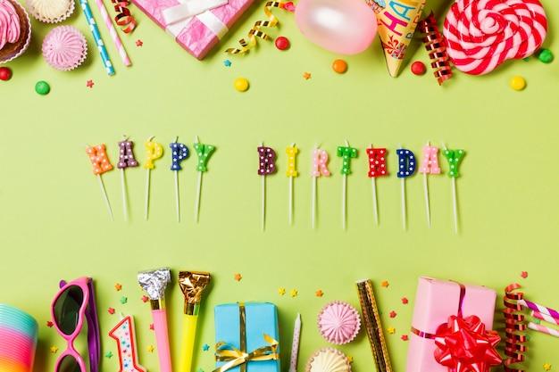 Velas del feliz cumpleaños con artículos de cumpleaños de colores sobre fondo verde