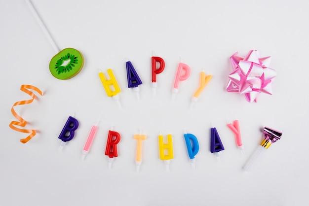 Velas de feliz cumpleaños con objetos coloridos