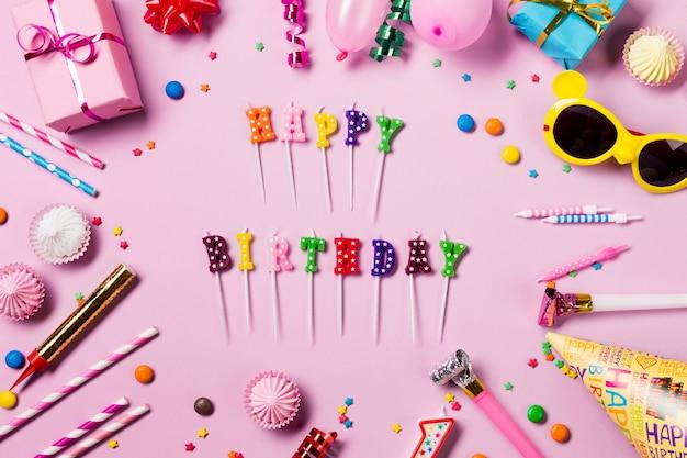 Velas de feliz cumpleaños rodeadas de serpentinas; gemas aalaw; sombrero de fiesta y cuerno de fiesta sobre fondo rosa