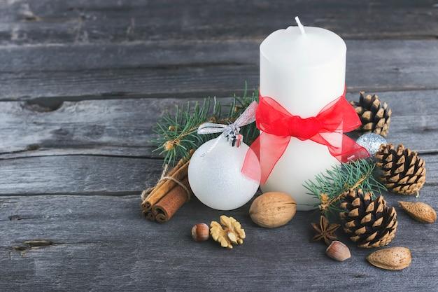 Velas festivas, abeto con árbol, piñas, nueces sobre una superficie de madera