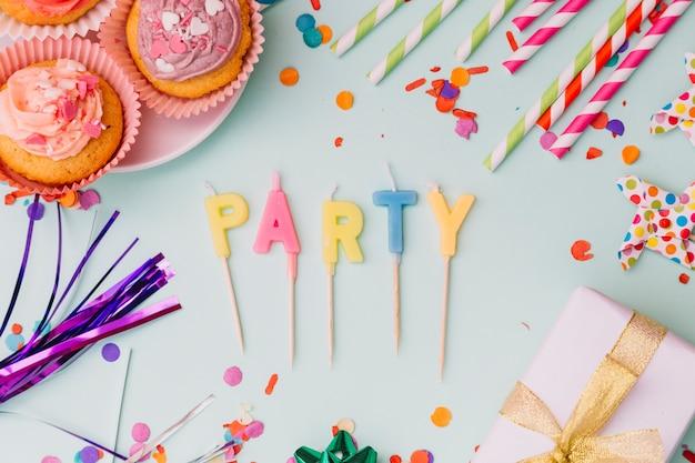 Velas de fiesta rodeadas de magdalena; pajitas de beber; apoyo y confeti sobre fondo azul