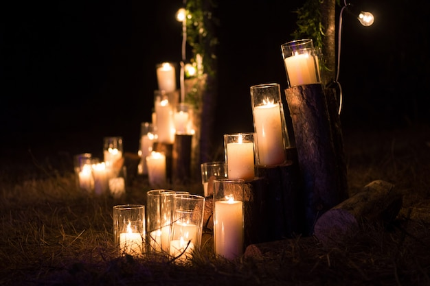 Velas en frascos de vidrio en la decoración de la ceremonia nocturna.
