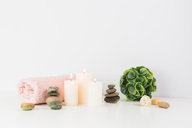 Velas iluminadas; toalla; piedras de spa en mesa blanca