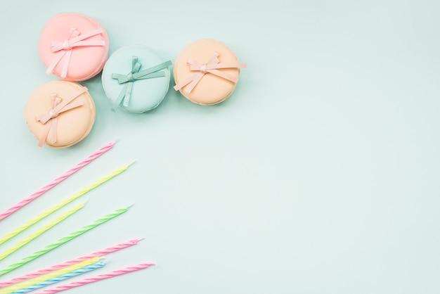 Velas y macarons rayados con el arco en el fondo blanco