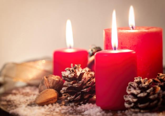 Velas navideñas rojas con piñas de abeto