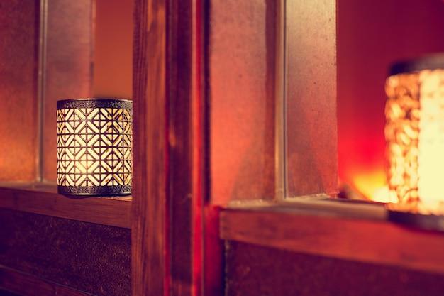 Velas orientales en madera, fondo oscuro colorido textura árabe.