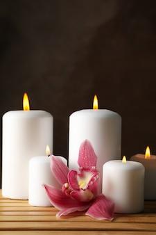 Velas y orquídeas en mesa de bambú