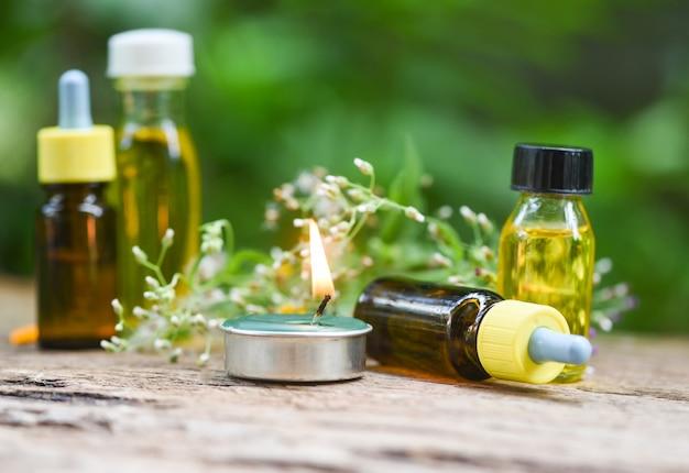 Velas perfumadas y aceites esenciales en mesa de madera.