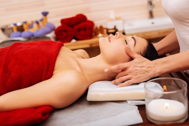 Velas perfumadas. mujer tranquila y soñolienta cubierta con una toalla roja en la camilla de masaje mientras el maestro trabaja con su rostro