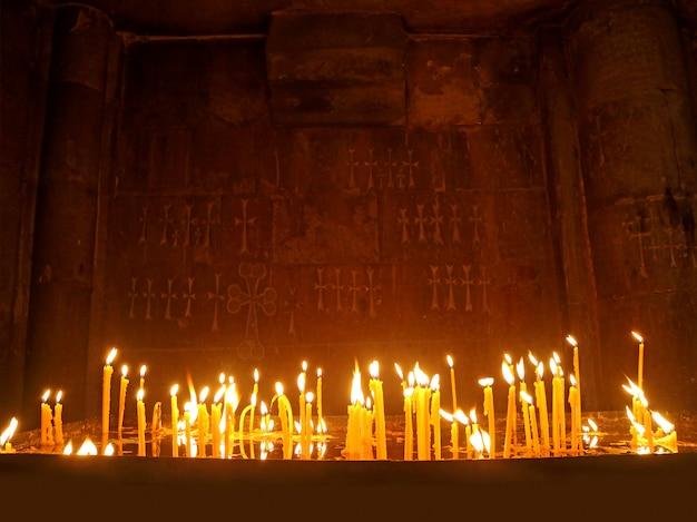 Velas que brillan intensamente en una oscura capilla de una iglesia ortodoxa