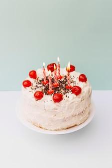 Velas de rayas encendidas en pastel blanco contra doble telón de fondo