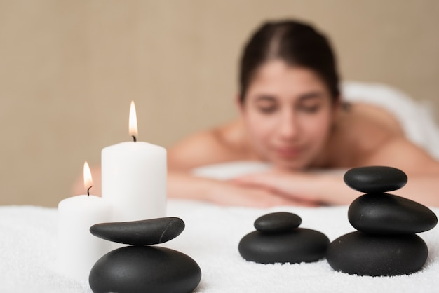 Velas y rocas de spa con mujer en spa