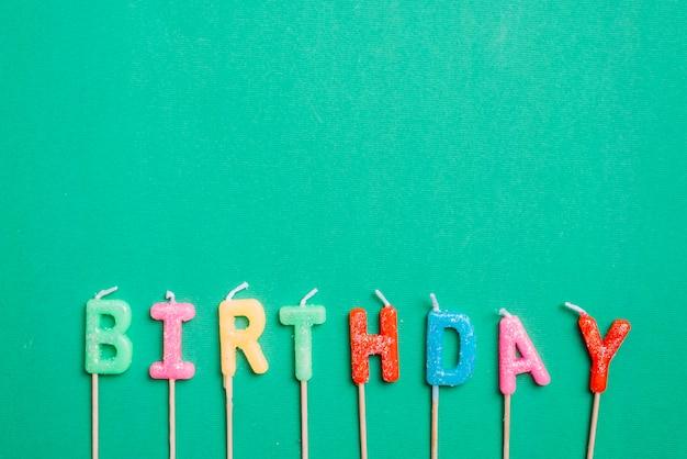 Velas de texto de cumpleaños con palo sobre fondo verde