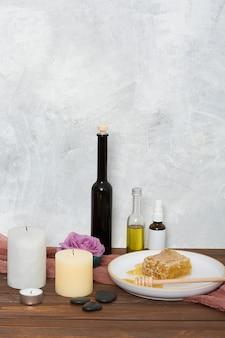 Velas el último; rosa; botella esencial; panal y cazo en el escritorio de madera contra la pared gris