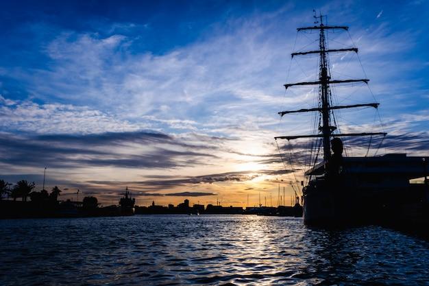 Un velero clásico amarrado al puerto en una hermosa puesta de sol.
