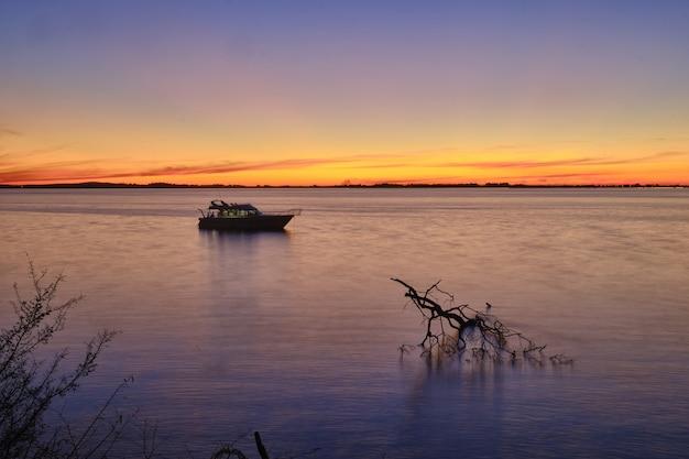 Velero en el hermoso océano tranquilo con la impresionante puesta de sol