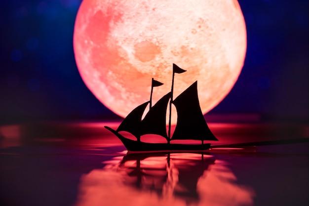 Velero con luna llena en la noche.