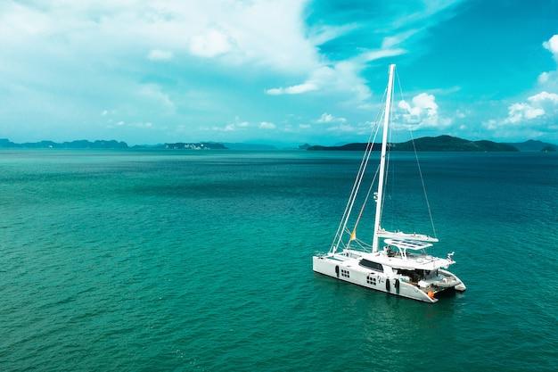 Velero yates con velas blancas en mar abierto. antena - vista de drone al velero en condiciones ventosas.